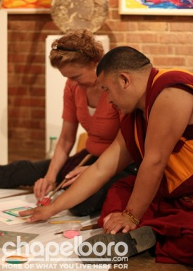 Lobsang Jampa helps a student during the sand painting class