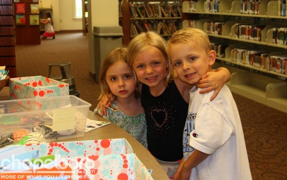 Emma Sloane, Caroline Elizabeth and Alden Eric stop by the library to pick up their prizes from the scavenger hunt