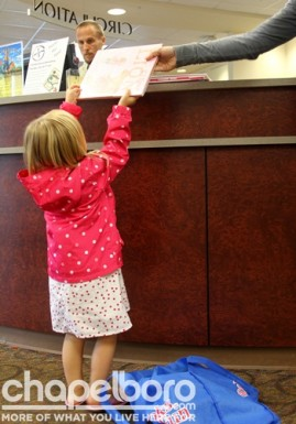 The check-out desk was so tall, Allison Claire needed a little help from her mom