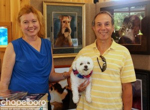 Artist Kim Werfel, Eric Werfel and Summer pose in front of Kim's beautiful paintings