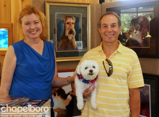 Artist Kim Werfel, Eric Werfel and Summer pose in front of Kim's beatiful paintings