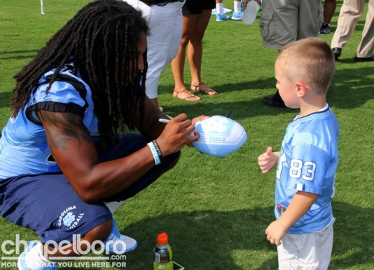 Tre Boston signs a football for Ethan Mahrle