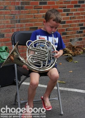 Nathaniel Percy tries out the french horn at the North Carolina Symphony's booth